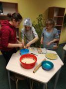 5.klases meitenes sadarbojoties ar skolotāju Sanitu cep dzimšanas dienas kūku.